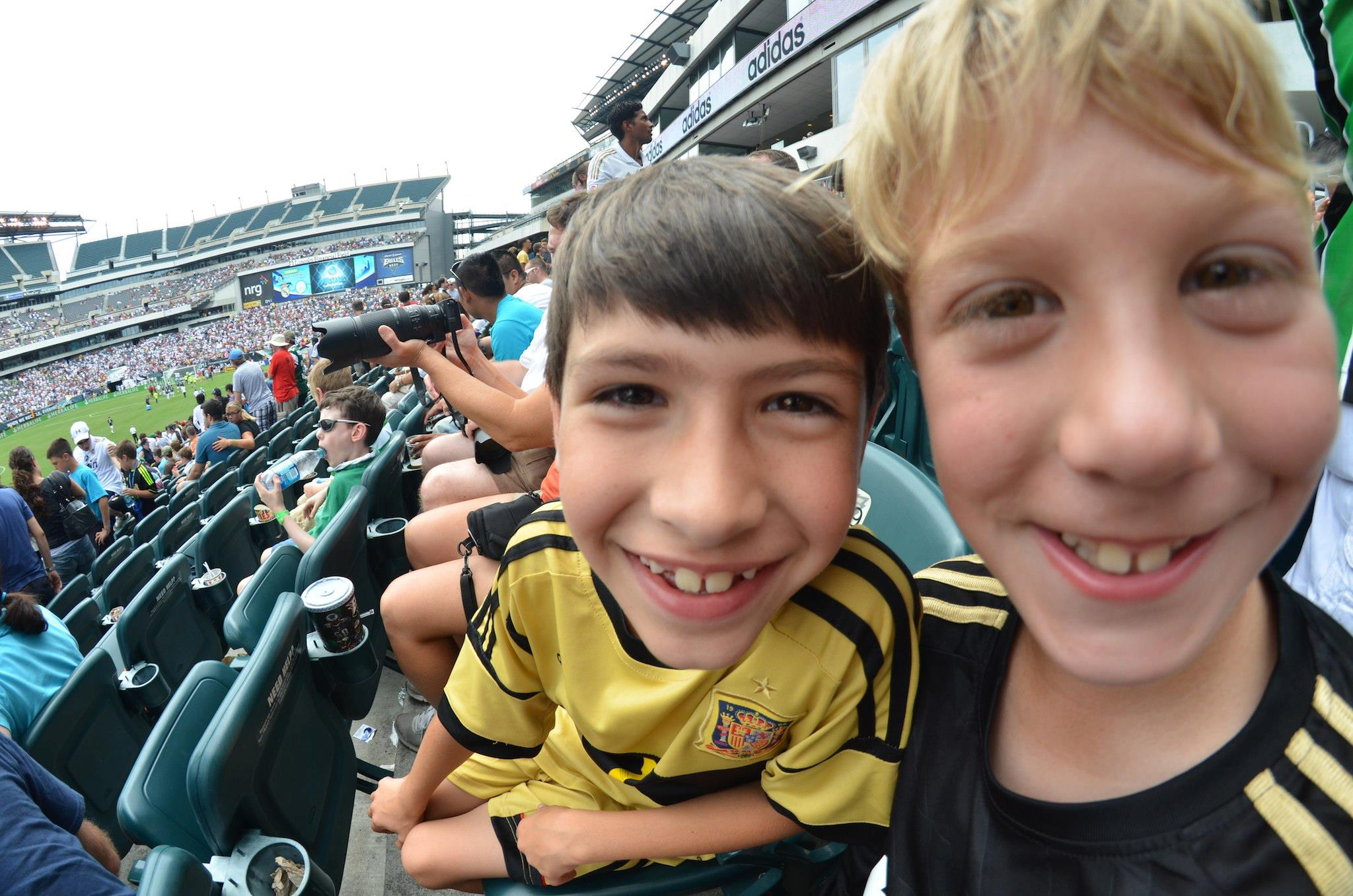 Mack and John watching Iker Casillas playing for Real Madrid v. Celtic. Mack is wearing his Iker Spain jersey.