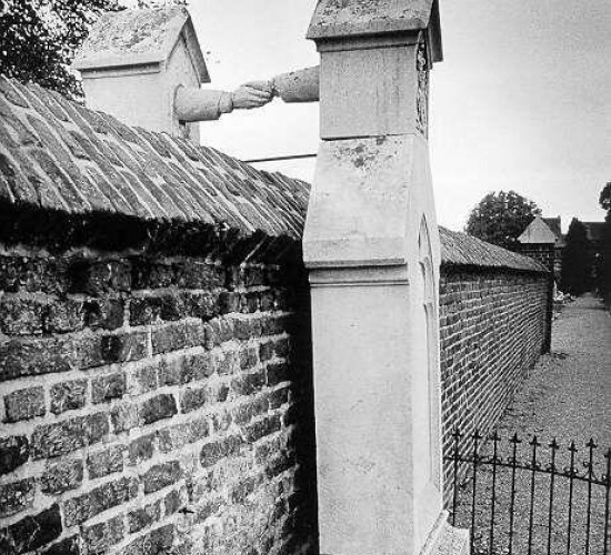 """The graves of Colonel J.C.P.H and Catholic noblewoman J.W.C Van Gorkum.  They were married in 1842.  In 1888, Van Gorkum died, she wanted to be buried next to her husband. Pillarisation (a form of religious and political segregation in Holland) was still in effect at the time, and according to the law, this was impossible.  His wife was buried on the other side of the wall, which was the closest she could get to her husband."""